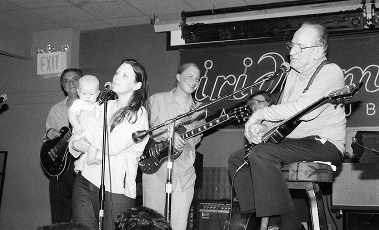 "Les Paul always let people set in at his regular Iridium gig on Broadway -- I would have loved to hear Mary Redhouse when she sang a Navajo grass dance with him, altho, I believe she started him out on ""Slow Boat to China"" -- This photo is Susan Tedeschi and Derek Trucks with their child, sitting in -- Susan sang ""Rock-a-Bye Your Baby With a Dixie Melody"" w/ Les's regular trio Nicki Parrott (bass) and Lou Pallo (guitar) -- they killed it, it was so good, next time I was in town I dragged Connie Crothers there to hear Les -- July 22, 2oo2 -- photo by Mark Weber (RIP Derek's uncle Butch died January 24, 2017)"