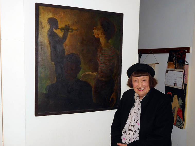 "Sheila Jordan in her apartment on 18th Street, Manhattan, with her painting by Virginia Cox (oil on board, early 60s) ""Virginia was one of the few black women painters on the scene then, nobody ever asks about that painting. That's Duke (Jordan) and Miles and me."" Photo by Mark Weber -- November 18, 2o16 -- It was Sheila's birthday and I was taking her out for late breakfast at our favorite neighborhood spot The Dish on 8th Avenue (between 20th & 21st Streets) afterwhich, we walked over to the Apple store so she could buy a cord -- In 1952 when Sheila left Detroit for New York City she and her Detroit friends Jenny King nee Devries, and Virginia Cox, all lived in an apartment in Gramercy Park (neighborhood on Manhattan at 21st Street and Lexington) ---- Over her kitchen sink she has a poster print of a tremendous painting by Bob Moses titled something like ""The Expanded Moment"" or ""The Expanded Musical Moment"" -- it might have been from a gallery exhibit Bob was having."