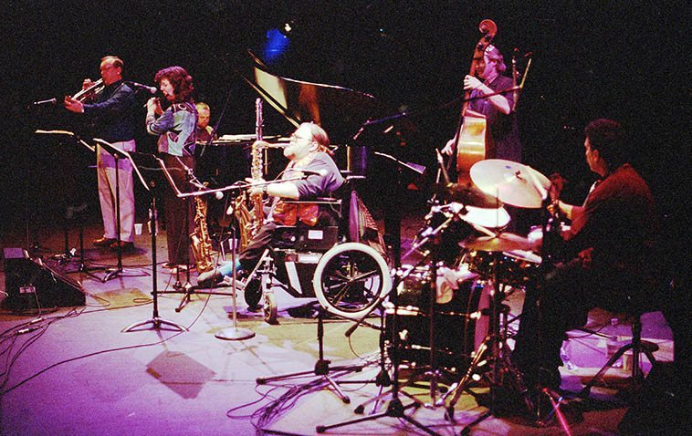 Come out of Seattle to play for us in Albuquerque: Bert Wilson & Rebirth: Bert on saxophones, Nancy Curtis (flute), Craig Hoyer (piano), James Zitro (drums), Jeff Johnson (bass), Syd Potter (trumpet) -- May 10, 1998 presented at South Broadway Cultural Center by Outpost Productions -- photo by Mark Weber -- the handbill says: Mulit-instrumentalist / Multi-phonic legend --------- We'll listen to some of his intricate music this day