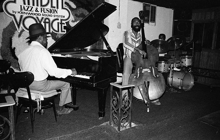 "The Gene Russell Trio at the Maiden Voyage, downtown Los Angeles -- August 23, 1980 ---- Whenever you got caught in L.A. around rush hour, rather than jump on whatever freeway it is you take to get home (there are ten different freeways that converge downtown), and sit in rush hour traffic and let your car over-heat (V8 engines need flowing air to cool them), I'd pop into the Maiden Voyage and kill an hour or two before jumping on the San Bernardino Frwy (10) back to Upland, one of the hundreds of ""bedroom communities"" that surround L.A. ------------ Here's Gene on piano (a great guy, I always had a good laugh with him); and fellow photographer Clarence Johnston on drums (he tipped me off that taking pictures at the boxing matches at the Olympic was a good score; and our man on bass: HENRY FRANKLIN the Skipper aka Nyimbo, who's still all over Southern California playing that bass and who I just saw in the 2017 restored version of MONTEREY POP (1967) on my favorite set of that flick with Hugh Masekela ----- I'll tell you, when I first saw this film back in 1969 at a little art house on Sunset Blvd, and that huge black African face of Mr Masekela came on the screen like 14-feet across it scorched my white butt back into my seat as he shouted that wordless healing chant, still one of the strongest parts of that documentary, and Henry pulsing and swaying the time like a wave"