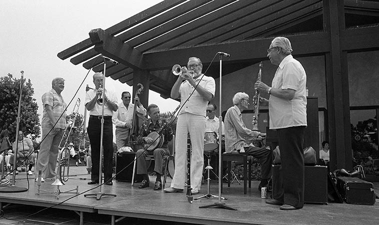 Joe Darensbourg & His Dixie Flyers jumping at Marina Del Rey, California -- June 7, 1981 ---- Left to Right: Phil Gray(trombone), Bill Stump(trumpet), Phil Stevens(bass), Nappy Lamare(banjo), Chuck Conklin(cornet), Ray Hall(drums), Bill Campbell(piano), and the master of the slap-tongue soprano saxophone Joe Darensbourg ---- photo by Mark Weber