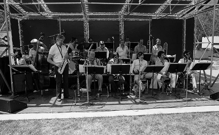 The Bill Holman Big Band: Trumpets: Bill Stapleton, Frank Szabo, Bob Summers, Don Rader; Trombones: Bob Enevoldsen(valve trombone, sunglasses), Jack Redman, Rick Pulver, Kenny Shroyer; Saxophones: Bob Cooper(tenor), Mike Altschul, Dan Higgins, Bob Shepherd, Kenny Berger(low end); Milcho Leviev(piano); Monty Bodwig(bass), Nick Ceroli(drums), Dave Levine(conga), Bill Holman (tenor & conductor) -- July 25, 1980 -- Bonaventure Hotel, downtown Los Angeles -- photo by Mark Weber -- Bill Holman is the quintessential Angeleno, drives sportscars, chooses his words carefully, has been active on the L.A. scene since the the late 40s, his weekly rehearsals at Local 47 are legendary for his artistic painterly winding travels his arrangements take ---- I got the best understanding over what he was about when he released his CD of Thelonious Monk arrangements in 1997 in that one already knows innately these renowned melodies, and hearing Holman's treatments gave you an insight into his methods, and how Monk's tunes had doorways that Holman opened up and stepped inside