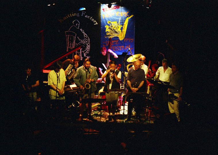 A group calling themselves Orange Then Blue at The Knitting Factory -- June 29, 1997 NYC w/ George Schuller(drums), Reid Anderson(bass), Jamie Saft(piano and accordion), Rufus Cappadocia(cello), Tom Varner(Fr-horn), Christoph Schweizer(trombone), Dave Ballou, Cuong Vu, Herb Robertson(trumpets), Andy Laster, Andrew D'Angelo, Tony Malaby(reeds) ---- photo by Mark Weber ----- and I bet the Music Witness was there, too, this being the years he (Jeff Schlanger) was in-residence drawing his two-handed chimeras -- We'll listen to a track from one of their five cds . . . .