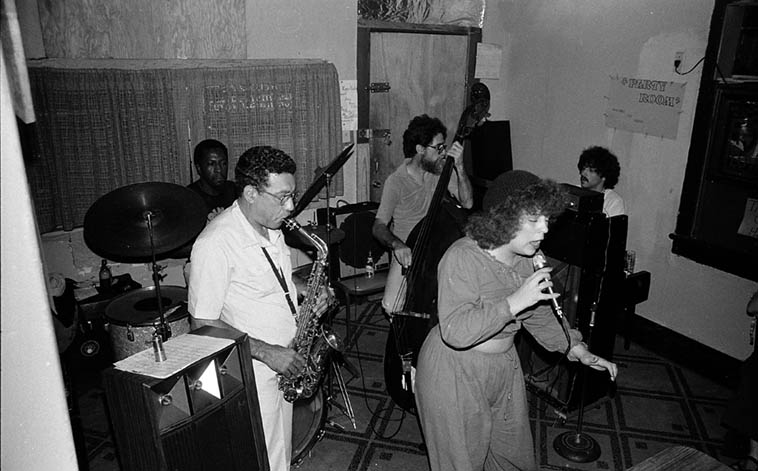"""Every jazz historian needs make pilgrimage to New Orleans. First time I went was Spring 1978 and I stayed six weeks and slept in flops and roominghouses ($2.50/night! I still have receipts). Summer of 1982 was my only other visit and I was a little more flush this 2-week trip, also, my brother Craig was working as a roustabout on the oil derricks in the Gulf so I had a place to stay. One night I took a cab to see the legendary James Black ---- I get in the cab and tell the (white) cabbie my destination ---- He pauses, then turns around and says: Are you sure? He figures me for an out-of-towner -- I say: Yup, shore am ---- He says: You're not exactly the right color to be in that ward (he's tipping a fellow member of the white race) ---- I say: It's cool ---- He says: It's your funeral ---- We arrive at the address, which is a converted wood frame house in a residential neighborhood: Alice's Keyhole Lounge (2214 S. Clairborne) ---- Cabbie turns around and says: Okay, I'm going to tell you one more time, I wouldn't go in there if I were you ---- I reassure him that the white race is not imperiled and pay him ---- I grew up in scrappy Cucamonga (Okies are crazy) and spent my weekends in the blues bars of Watts, """"Dicey"""" was my middle name ---- And just as I knew it would be: All was happy-to-see-you handshakes and come-right-in (after Alice checked me out through the keyhole). One of the truisms of us music nuts is we're a small club, color is secondary. Ears and a brain are the only requirement for membership. James Black(drums), Mary Bonnett(vocal), Warren Bell Sr(alto), David Torkanowsky(subbing for Eddie Collins on piano), Rusty Gilder(bass) -- July 3, 1982 photo by Mark Weber"""