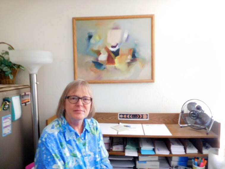 A slightly blurry Membership Accounts Exec Cris Nichols in her office at KUNM with painting by her mother -- September 7, 2o17 -- photo by Mark Weber with camera he has since tossed out the window -- Her father Wayne Nichols played trumpet in Charlie Barnet's band, and in Bob Wills Texas Playboys!