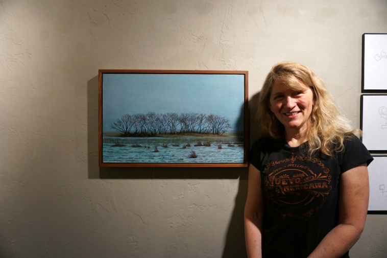 "I've always loved Susan Holmes posters she makes for the band Alpha Cats with whom she plays bass, and I'll take credit for tipping the curators to get her into this group show Musicians Making Art, but I didn't know she was an exquisite oil painter, whew, so much talent ---- That's Susan and her painting ""Bonanza Creek Cottonwoods, Looking East"" (2o17) ----- ""It's Kansas,"" she told me – photo by Mark Weber – July 15, 2o18 (you can see my 3 doodles To Susan's right)"
