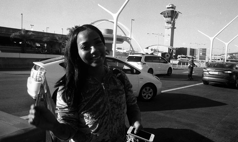 This young lady at LAX saw me with my old cameras shooting & rolling (you have to clear it out of your camera before sticking it into those x-ray machines at the TSA checkpoint) and asked what I was doing, and I told her I had to get the film out of my cameras, and typically everybody is amazed I'm still shooting film, I said Look into the camera and snapped this one – Her name is Omri Randolph, I forgot where she was heading, I was flying back to Albuquerque ---- February 7, 2o18 – photo by MW