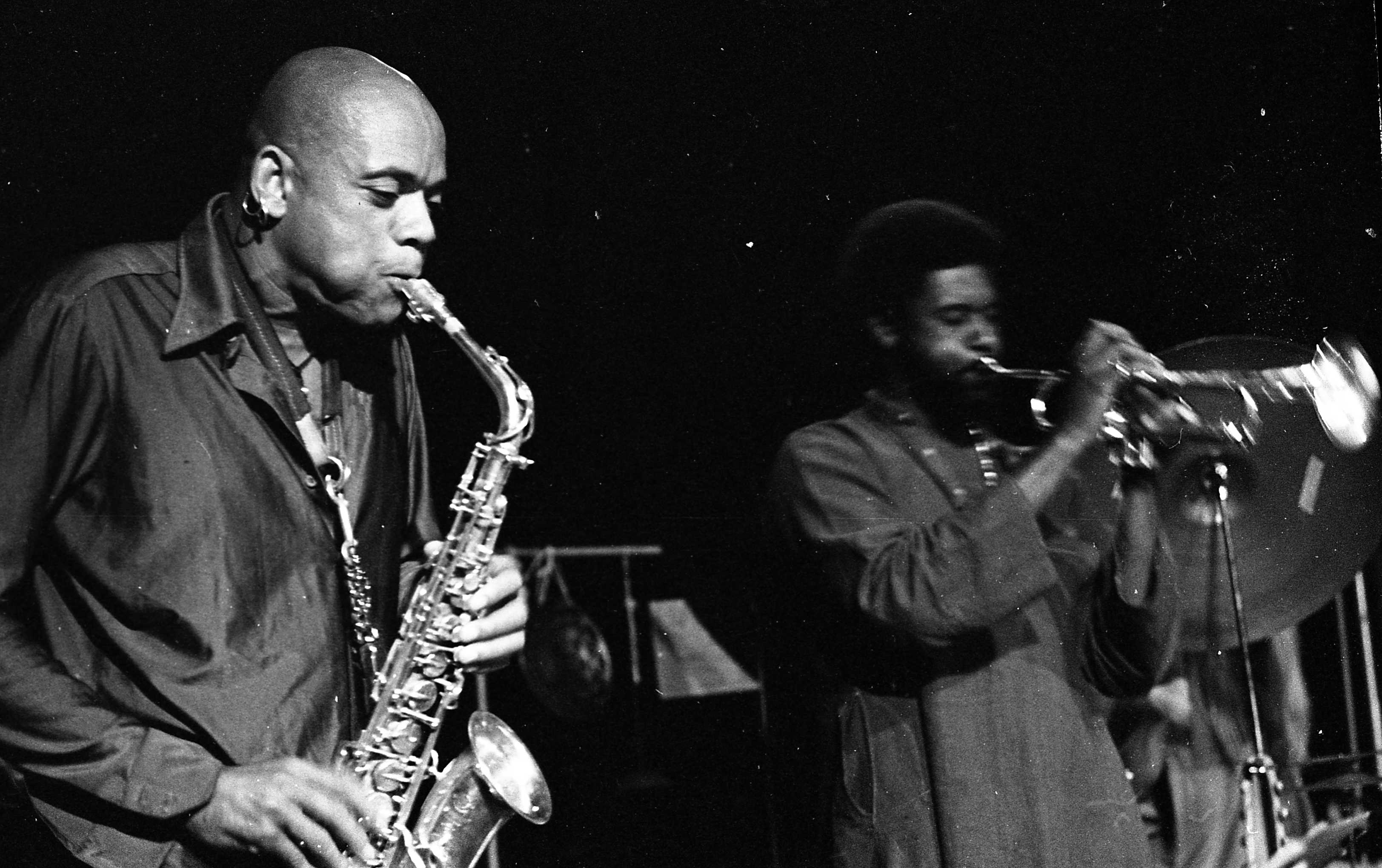 """This is a rare shot of what Julius called The Janus Company -- a trio of Julius Hemphill (alto saxophone, maybe flute), Baikida EJ Carroll (trumpet), and my brother Alex on drums. They played a mere handful of concerts in the U.S. -- in Los Angeles (seen here at the Century City Playhouse), in Berkeley at a place called Mapenzi, and later in Philadelphia (at The Foxhole maybe?) with Abdul Wadud added on 'cello. I think this photo may portray the first gig Alex ever did with Julius. As was often the case, when someone asked creator/curator of the concert series Lee Kaplan who in Los Angeles should play drums on a concert, he recommended Alex, and Julius LOVED Alex's playing right away, which led to those future gigs. I think Alex was about 22 years old at the time (which means I was, too). They actually recorded an album for Lee's emerging Aten label which was never released. But they went on to tour Europe -- a tour which did not go especially well as I understood, owing to Julius' self-destructive impulses and some other complications. Alex and I had already been made aware of Baikida's playing from Julius' recording """"Dogon A.D."""" from his St. Louis years, and Baikida was phenomenal on trumpet as well as being a sweet human. He also made some really fantastic records of his own around this time. Years after The Janus Company, after Julius had had to have one of his legs amputated at the knee (an alcoholic/diabetic gang green scenario), Julius took some down time at his aunt's in Oakland CA and got himself together, and during this time he contacted Alex about his desire to start an electric band with him, along with Jumma Santos (percussion), yours truly on guitar, and a bassist. Julius asked Alex who he recommended, and he suggested Steuart Liebig (who eventually started calling himself """"Steubig"""" around this time for some reason I have never understood, in spite of his repeated explanations). This became Julius Arthur Hemphill and the JAH Band (as in Julius Arthur """