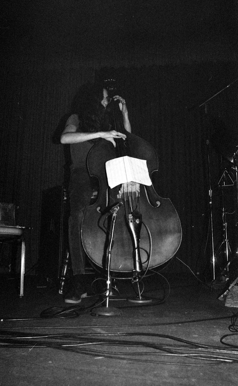 "Eric ""preparing"" his bass for a percussion jam or something with a sheet of music paper! --------------photo by Mark Weber of Eric Von Essen – May 15, 1982"