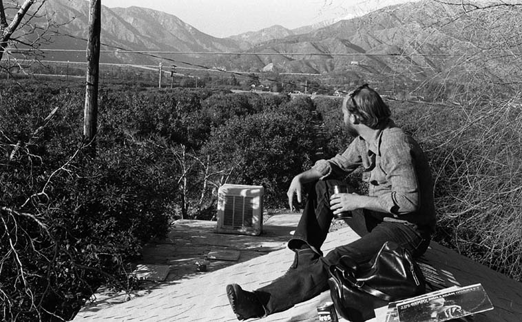I grew up under those mountains: The San Gabriels, and that's Mt Baldy and the San Antonio Dam, and my drinking buddy Cary Adams who I've known since 7th grade ----- Those are the lemon groves ----- citrus was everywhere in those days ----- January 1980 Upland, California ----------- see the Gerry Mulligan Lp in the foreground (I don't know why we had it up on the roof with us? Maybe we had some speakers up there, too?) – photo by Mark Weber