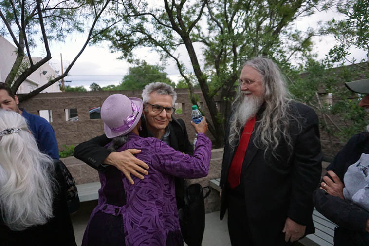 "Micky Patten gives singer Carla Van Blake Terwilliger a hug while Lewis Winn chaperones ---- Outpost patio – May 9, 2o19 ---- photo by Mark Weber ---- Carla sang ""Alfie"" she and her guitar playing husband Steve immigrated to Albuquerque 2017"