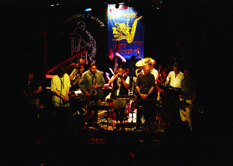 The group known as Orange Then Blue – Knitting Factory NYC June 29, 1997 – You can barely see drummer George Schuller in this shot – Ensemble included: Jamie Saft(piano), Rufus Cappadocia(cello), Tom Varner(Fr-horn), Christoph Schweizer(trombone), Dave Ballou & Herb Robertson & Cuong Vu(trumpets), Andy Laster & Andrew D'Angelo & Tony Malaby(reeds), Reid Anderson(bass), who is on tuba? And who is on accordion? ---- photo by Mark Weber