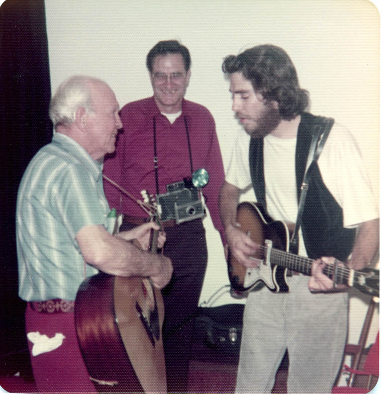 Grandpa Harry Matthew & MW w/ guitars in my Mom's kitchen while Dick Trumbull watched with is Polaroid camera – Dick is family visiting from Wichita, Kansas, circa 1973