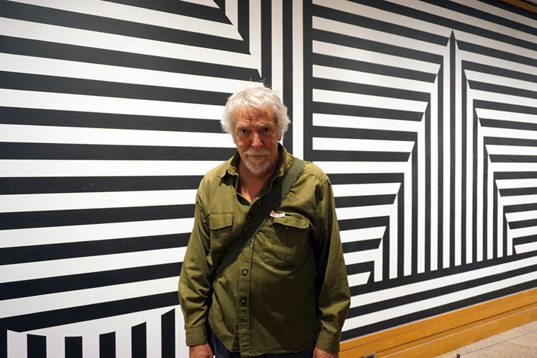 That's me in my camo outfit at the Metropolitan Museum of Art snapped by Carol Liebowitz September 30, 2o19 ---- My guess is: that wall design is by Victor Vasarely (1906-1997), if not, it's certainly influenced by his amazing op art of which I am a giant fan