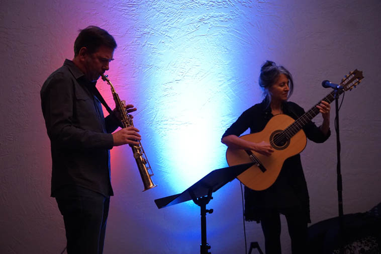 Chris Jonas & Janet Feder in duet in Corrales, New Mexico ---- December 7, 2o19 @ Live at Thrive (produced by Roch Doran) ---- photo by Mark Weber . . . . from my notebook: Janet's concert last night very even-temper'd, quiet, quietness being one of her compositional elements, everything cohered, if there was disjunction it was of the sort you'd find in an M.C. Escher, very intricate, with waterfalls that flow down back around itself to waterfall continuously, coalesced, all in agreement, mirror'd images, contrast and recapitulation and uniformity, parallelism, balance, counterbalance, whirling in, all things drawn to the center, together, pulling together as it turns quietly, like a Calder mobile . . . counterbalance best word to describe it, and Chris masterfully found his way into her music beautifully, he being a guest on this
