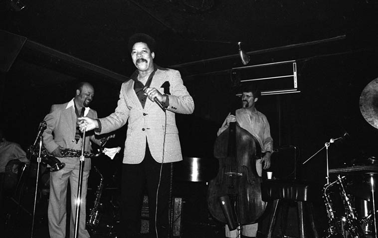 """Tom Albach (producer of Horace Tapscott recordings, age 94) asked me the other day who was that comedian who used to work The Parisian Room, and I immediately said REYNALDO REY! And Tom said, """"Yeh! Man he was filthy!"""" This was the era depicted in Eddie Murphy's new biopic DOLEMITE IS MY NAME AND FUCKING UP MOTHERFUCKERS IS MY GAME of the pimp-cum-stand-up-comedian Rudy Ray Moore---- That's Red Holloway(tenor) and Harvey Newmark(bass) – Parisian Room, corner of Washington & LaBrea, June 13, 1980, I've been told Parisian Room is tore down and now there's a post office there, sure was a lot of good music there in those days ---- photo by Mark Weber"""