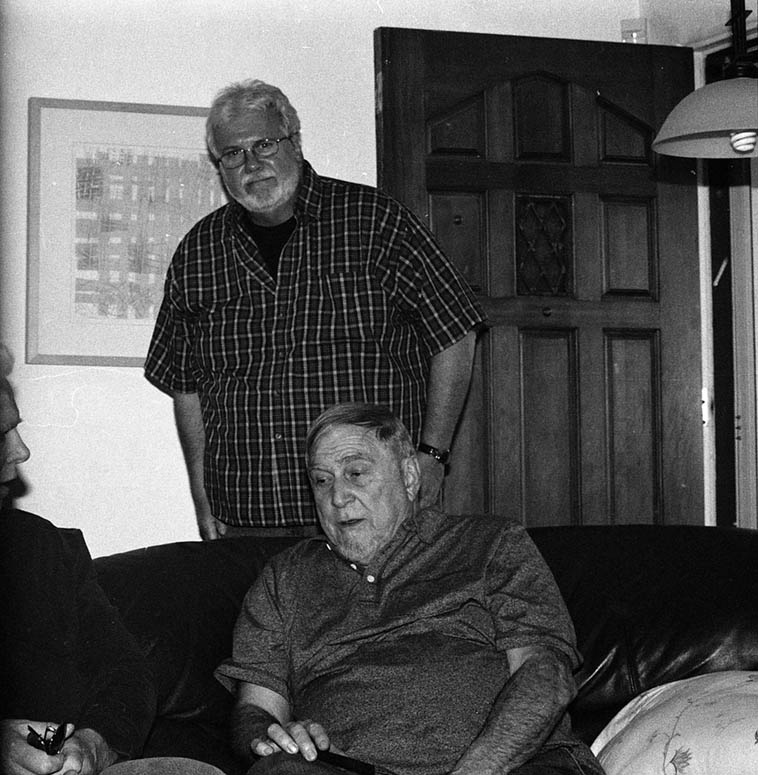That's the tip of Bill Payne talking with Charley Krachy with John staring at the camera here at 725, a little party we had for the visiting New Yorkers and Las Vegans May 4, 2016 ----- Everybody in town for the INTERLACE concerts at Outpost I produced and John was an assist & advisor – photo by Mark Weber