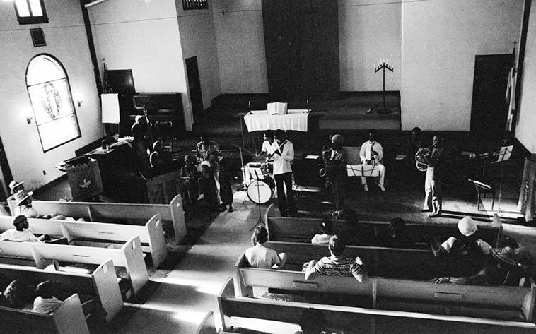 Pan African Peoples Arkestra – 1980: David Bryant(bass), Linda Hill(piano), child choir + Adele Sebastian & JeJeGr, Billy Hinton(drums), Aubrey Hart(flute), Sabir Matteen(tenor), Ufahamu Uweizi(alto), Fundi LeGogn(Fr-horn) ---- photo by Mark Weber