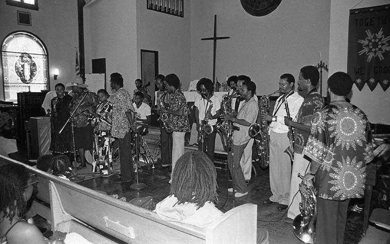 "Pan Afrikan Peoples Arkestra ---- June 28, 1981: Horace Tapscott (piano), Clortnee & Linda Hill & JuGeGr (vocals), David Bryant (bass) Louis Spears (cello) Fritz Wise (drums), saxophones: Ufahamu Uweizi, Arthur Wells, Sabir, Dr James ""Jimmy"" Benson, Gary Bias, Herbert Callies (alto-cl.); Moises Obligacion (conga), Fundi (Fr-horn); and my field notes say Ernie Roberts (bass-clarinet) but is that him on baritone sax? All surrounding the angel Adele Sebastian (flute)---- photo by Mark Weber"