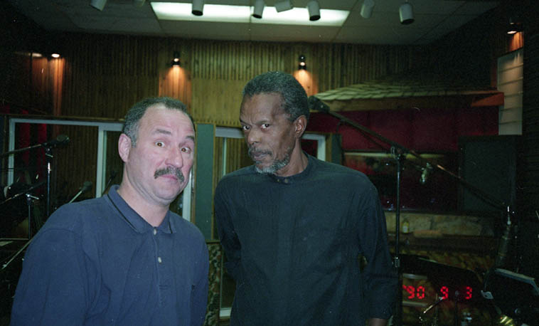 "I was in town and scheduled to be at this Horace Tapscott Octet session but my wife had an accident and that took precedence ---- SO, the tuba chair on this date, William Roper, took this shot of producer David Keller and HT ---- December 21 or 22, 1995 Los Angeles ------ Memory Fragment: Horace always tripped me out that he never smoked joints down to the tip end. You'd see perfectly good roaches around his pad in the ashtrays with the cig butts. And I don't gather he smoked them later because when we were outside and the joint we'd been passing back & forth was down to the nub, he tossed it. I think it was beneath him to use a roach clip. Never saw him with one. Was it a Los Angeles hipster thing? Because, the two times I ever smoked with Dexter he did the same. Tossed the roach into the ashtray. (I saved one of his roaches and had it encased and left it on our coffee table as a conversation piece.) Well, us broke Sixties insurrectionists used roach clips. Or, we rolled up the cover to a matchpak into a tube. Disposable. No evidence except our pleasant moods. We'd keep close when the pigs mispronounced their new big word paraphernalia. Horace's thing could be a throwback to earlier times when weed was more plentiful. He said, ""We got it from the Mexicans, they grew it in their backyards."" I grew my own, too, in a box on the roof in the alcove of an awning hidden by a tree. That was leaf weed, a low-level buzz. Horace never disparaged those joint I gave him, we only smoked those in times of drought, probably reminded him of the backyard weed of his teenage years. By the 70s it was Tom who kept us supplied with state-of-the-art smoke."