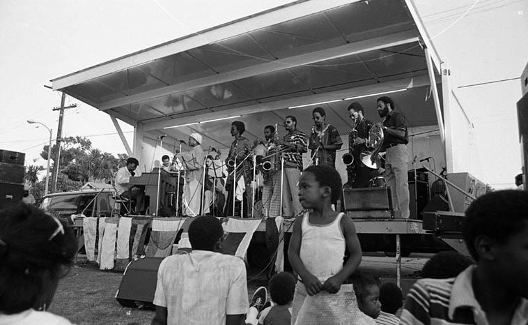 Pan Afrikan Peoples Arkestra this day was: Al Hines, Roberto Miranda, David Bryant(basses), Linda Hill(alternating with HT on piano), Adele Sebasian(flute), Fritz Wise(drums), Arthur Wells(tenor), Herbert Callies(alto clarinet), Fundi LeGohn(Fr.horn), Moises Obligacion(conga), Ufahamu Uweizi(alto), JujeGre(vocal), Cortnee(vocal), Marla Gibbs(vocal), Bruce Bidlack(soundman), and I missed the names of the baritone sax, and the bass clarinet, and one of the tenor players ---- July 11, 1981 --- photo by Mark Weber
