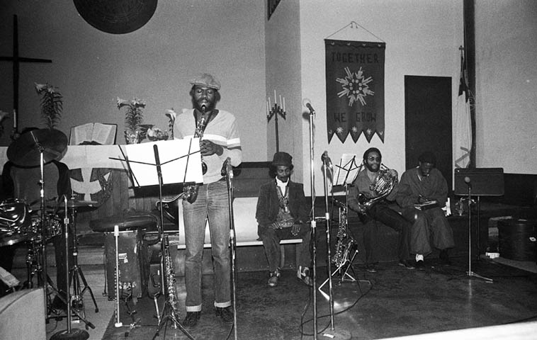 Gary Bias takes a solo at Immanuel United Church of Christ ---- Fritz Wise(drums), seated: Ufahamu Uweizi(alto), Fundi LeGogn(Fr.horn), JuJeGr(vocalist) ---- Pan Afrikan Peoples Arkestra ---- April 26, 1981 ---- photo by Mark Weber