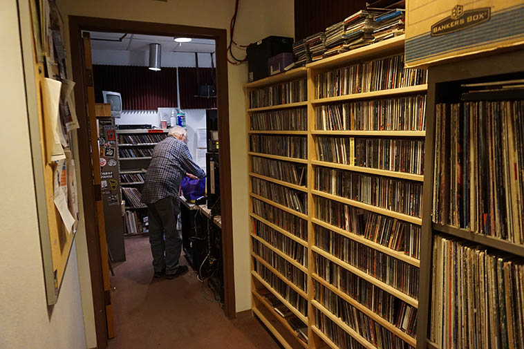 Arlen packing up after the show --- Hallway looking toward control room KSFR July 1, 2019 ---- photo by MW